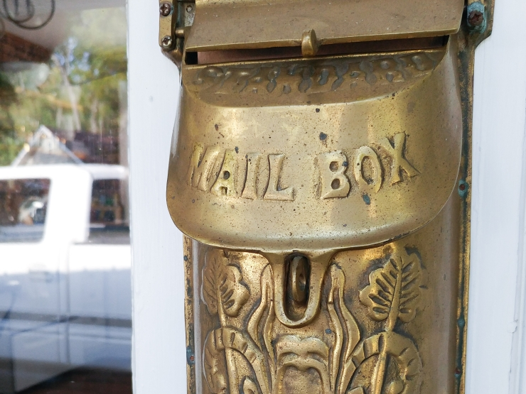 An antique brass mailbox welcomes guests to the Cozy Blue Cottage