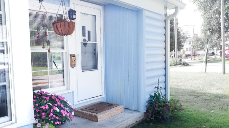 The front porch of the cozy blue cottage